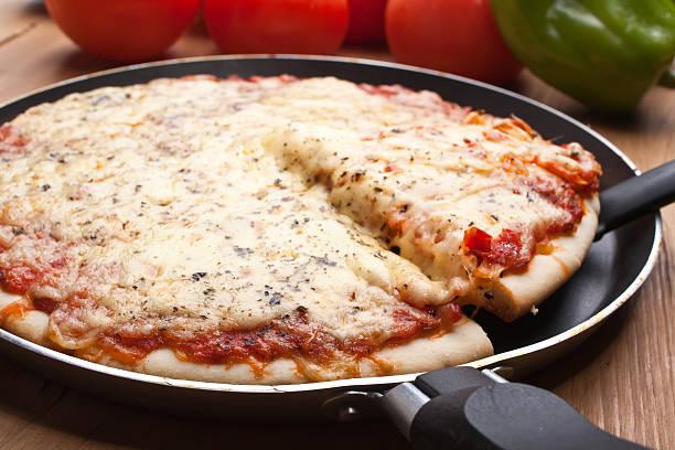 Pizza margarita in a frying pan stock photo