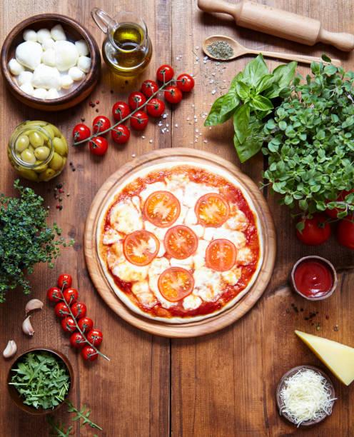 pizza margarita auf einer holzplatte und die zutaten, aus der es hergestellt wird. italienisches essen hintergrund. ansicht von oben. flach zu legen. platz für text zu kopieren. - low carb pizzateig stock-fotos und bilder
