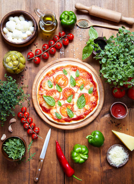 pizza margarita auf einer holzplatte und die zutaten, aus der es hergestellt wird. italienisches essen hintergrund. ansicht von oben. oregano, parmesan, olivenöl, mozzarella, rucola im rahmen - low carb pizzateig stock-fotos und bilder