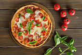 Pizza Margherita on a cutting board, fresh tomatoes and basil on wooden table, top view