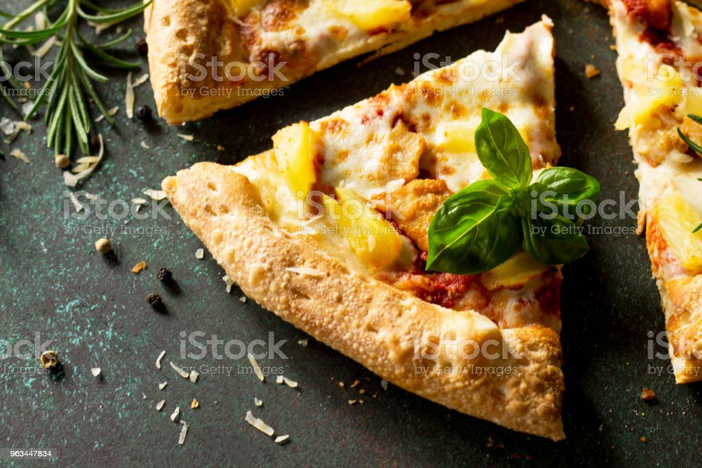 Pizza menu. Delicious hot Hawaiian pizza with chicken, pineapple and cheese. Delicious traditional Italian pizza on on a dark stone or concrete background. - Zbiór zdjęć royalty-free (Ananas)