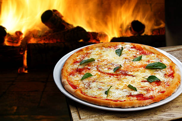 Pizza on a table with a fire in the background  stock photo