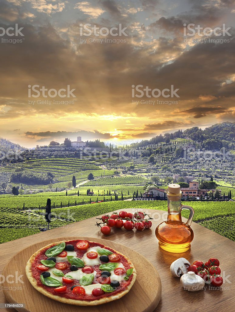 Pizza on a table with a sunset view of a vineyard in Italy stock photo