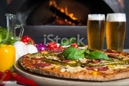 874991150istockphoto Pizza ordered in traditional italian restaurant with beer company 498892546