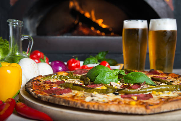 Pizza ordered in traditional italian restaurant with beer company Dish which consist of delicious italian pizza made form a lot of fresh ingredients and glass of cold beer. pilsner stock pictures, royalty-free photos & images