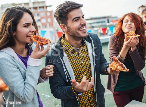 Happy young people eating pizza on the roof party