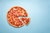Pepperoni pizza on a blue background top view. Traditional italian food. Flatlay with a home-baked pizza with hot pepperoni and mozzarella.