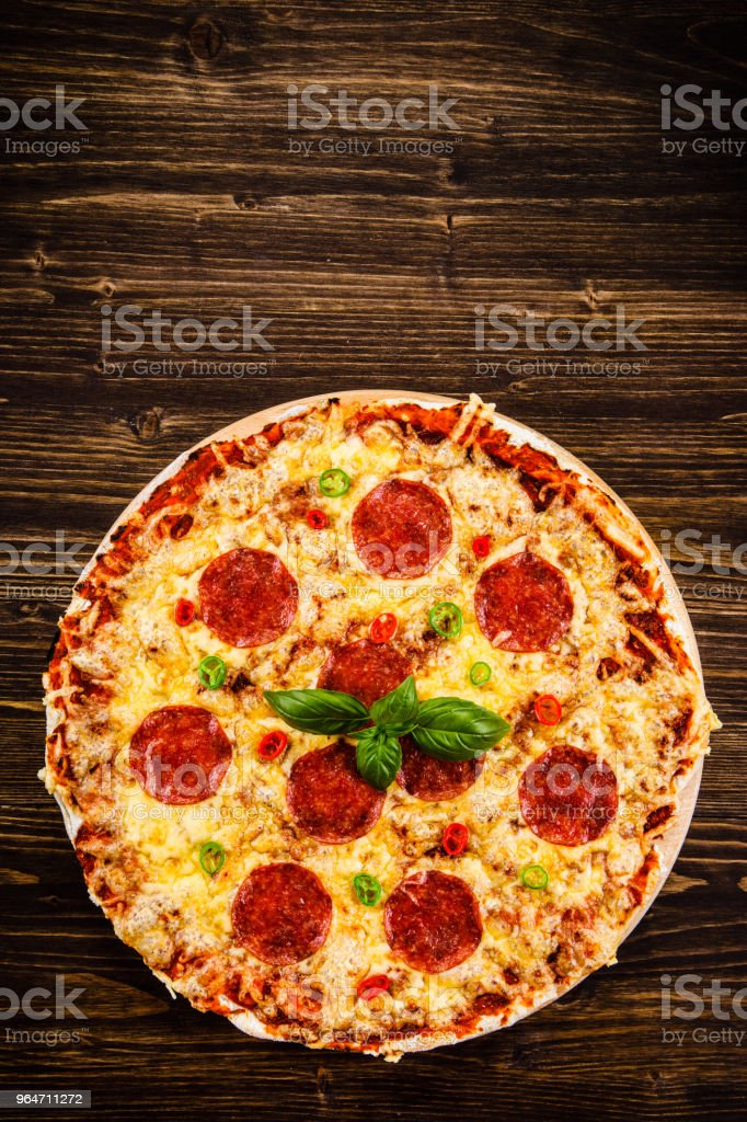 Pizza pepperoni on wooden background royalty-free stock photo