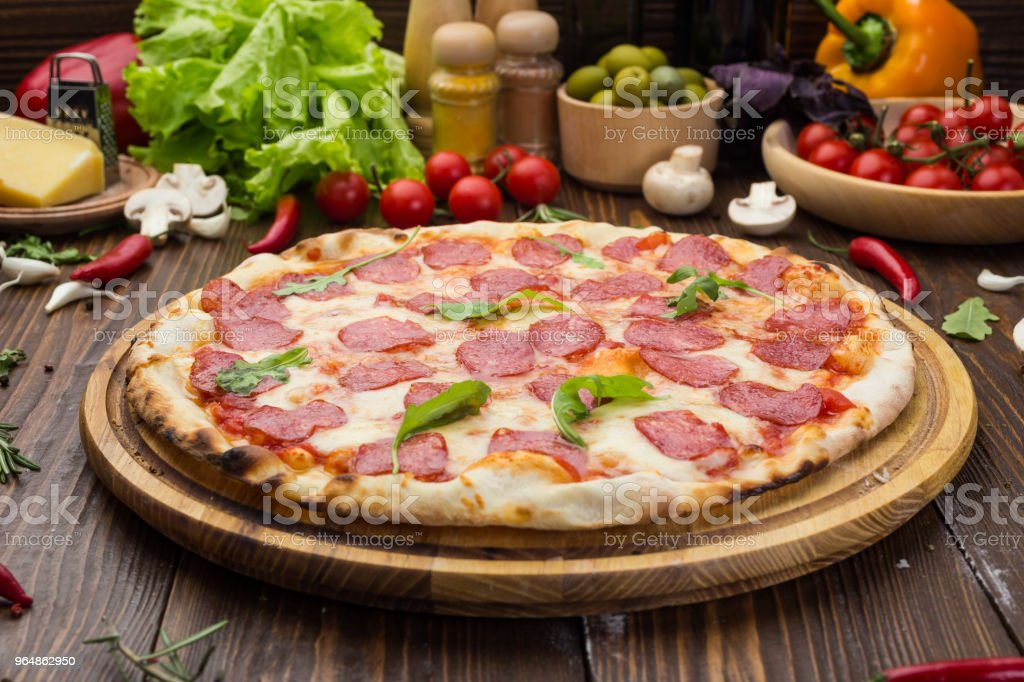 Pizza pepperoni with mozzarella cheese, salami and arugula on wooden background royalty-free stock photo