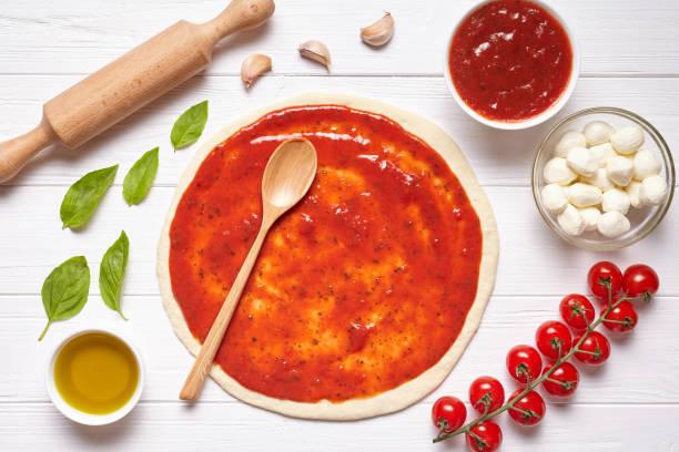 pizza vorbereitung. backzutaten auf dem küchentisch: gerollt teig mit tomaten-sauce - low carb pizzateig stock-fotos und bilder