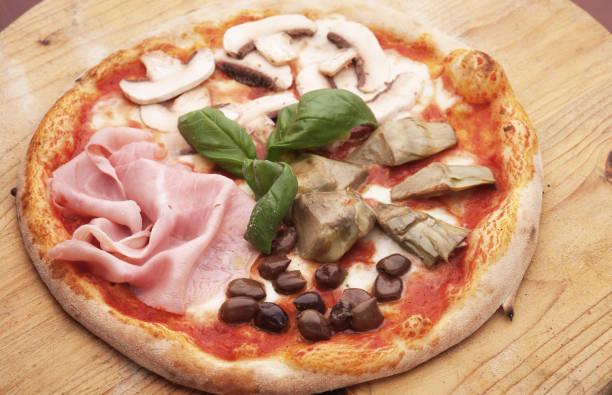 Pizza Quattro Stagioni, with ham and artichokes stock photo