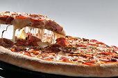 Pizza de mussarela com calabresa sendo servida em fatia com o queijo derretendo , bem apetitosa e saborosa assada no forno a lenha