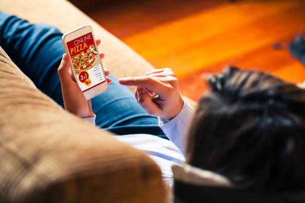 pizza shopping app in einem handy-bildschirm. frau, die das smartphone in der hand hält. - bestellen stock-fotos und bilder