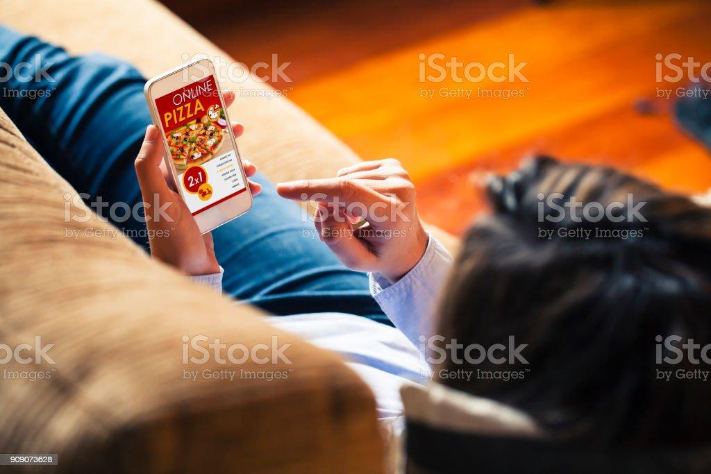 Pizza shopping app in het scherm van een mobiele telefoon. Vrouw met de slimme telefoon in de hand. foto