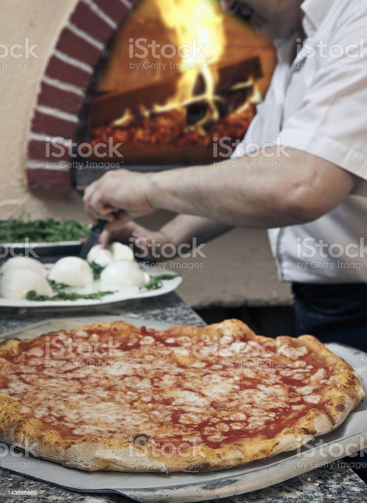 Pizza sitting on spatula in kitchen stock photo