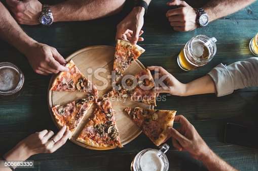 Friends having pizza in a restaurant. Top view.