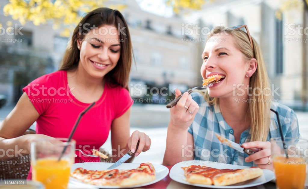 Pizza time. Young girls eating pizza in a cafe. Consumerism, lifestyle stock photo