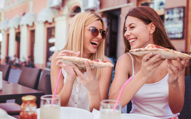 Hora da pizza. Jovens garotas comendo pizza em um café. Consumismo, estilo de vida - foto de acervo