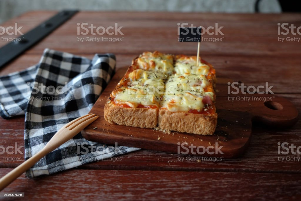 Pizza toasted bread with tomato sauce and ham cheese selective focus, picture vintage style stock photo