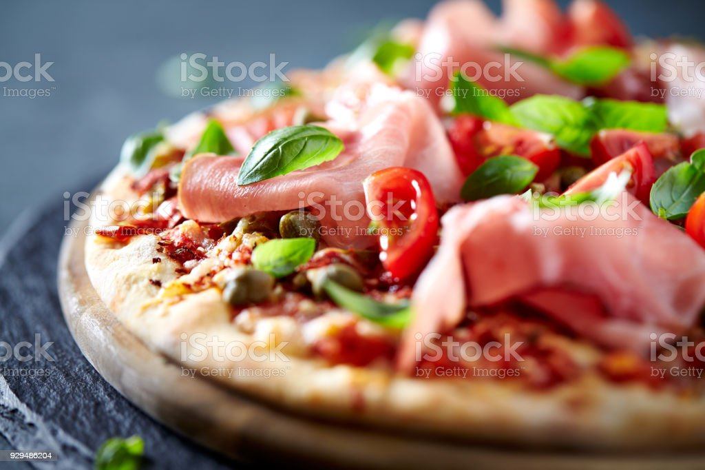 Pizza topped with black forest ham, capers and tomatoes stock photo