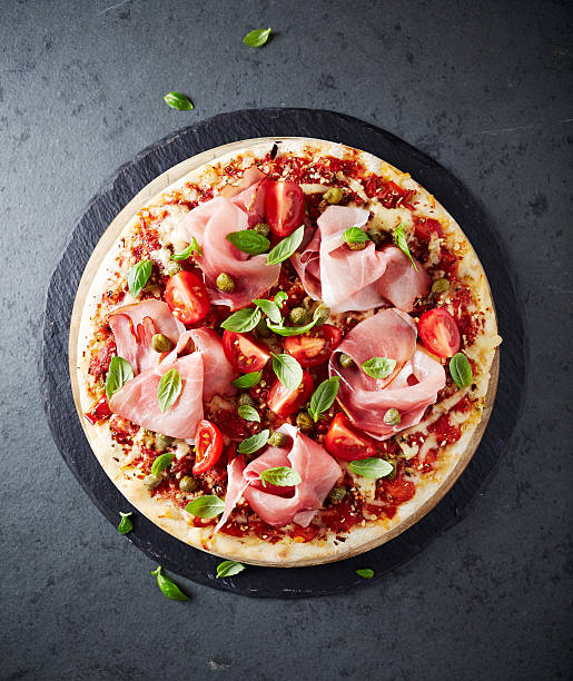pizza topped with black forest ham, cherry tomatoes and capers - parma jambonu stok fotoğraflar ve resimler