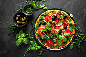 istock Pizza. Traditional italian pizza with green basil pesto sauce, top view 1184207726