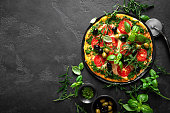 istock Pizza. Traditional italian pizza with green basil pesto sauce, top view 1184207811