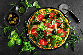 istock Pizza. Traditional italian pizza with green basil pesto sauce, top view 1184207839