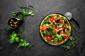 istock Pizza. Traditional italian pizza with green basil pesto sauce, top view 1184207973