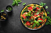 istock Pizza. Traditional italian pizza with green basil pesto sauce, top view 1184208538