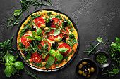 istock Pizza. Traditional italian pizza with green basil pesto sauce, top view 1184209460