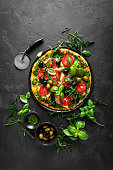 istock Pizza. Traditional italian pizza with green basil pesto sauce, top view 1184217146