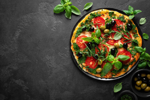Pizza. Traditional italian pizza with green basil pesto sauce, top view stock photo