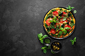 istock Pizza. Traditional italian pizza with green basil pesto sauce, top view 1202699207