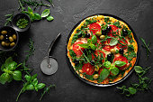 istock Pizza. Traditional italian pizza with green basil pesto sauce, top view 1202700252
