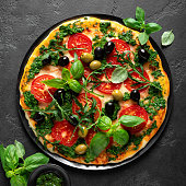istock Pizza. Traditional italian pizza with green basil pesto sauce, top view 1202700350