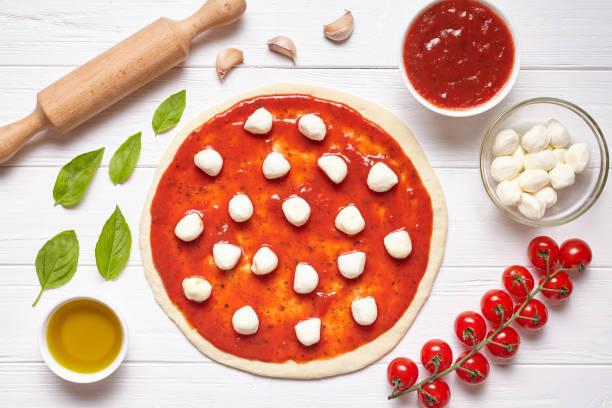 traditionelle zubereitung von pizza. zutaten auf dem küchentisch: gerollt teig mit tomaten-sauce - low carb pizzateig stock-fotos und bilder