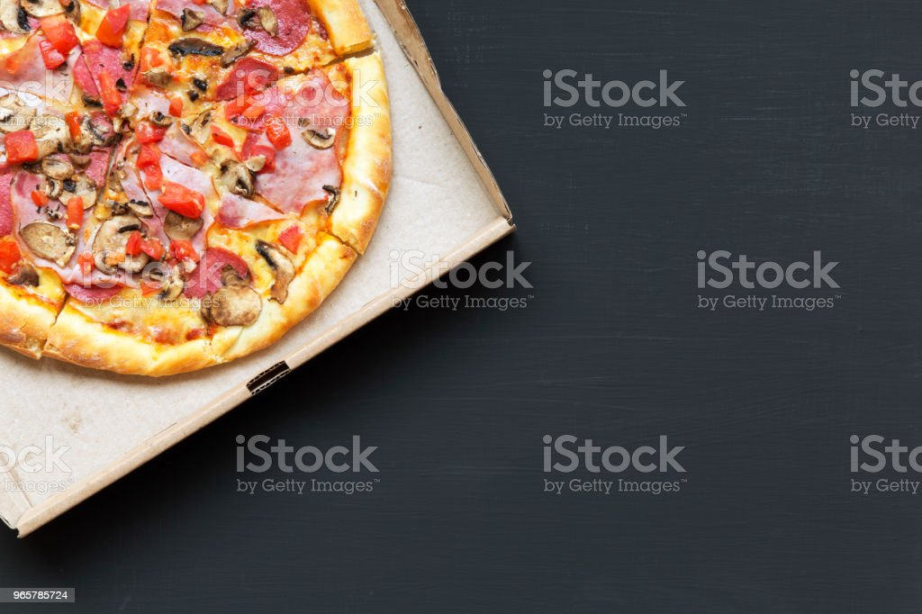 Pizza with bacon, tomatoes, salami, cheese and mushrooms in a cardboard box on dark background. Copy space. From above, flat lay. - Royalty-free Above Stock Photo