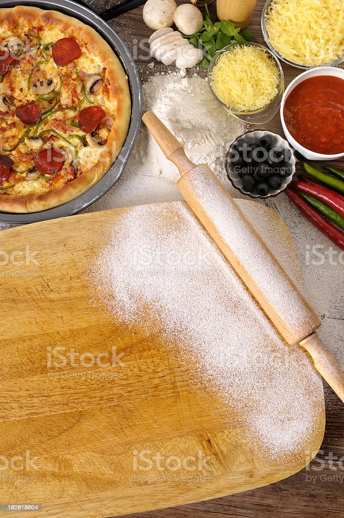 Pizza with chopping board and ingredients royalty-free stock photo