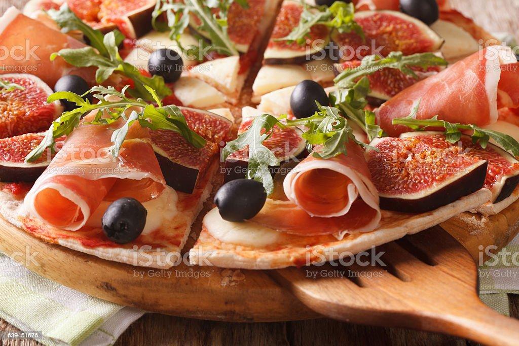 pizza with figs, ham and mozzarella macro on a board stock photo