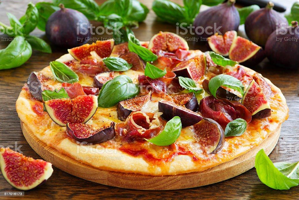 Pizza with figs, prosciutto and mozzarella. stock photo