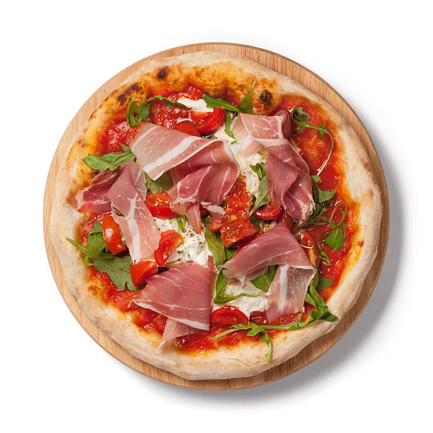 Pizza with  fresh tomatoes, arugula, Parma ham on wodden plate stock photo