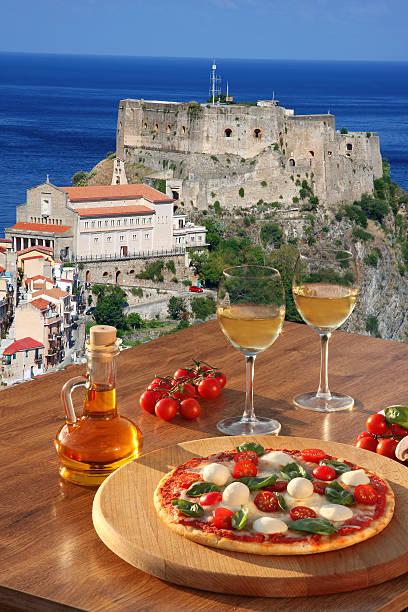 pizza con bicchieri di vino contro scilla castle, calabria, italia - foto di tropea foto e immagini stock