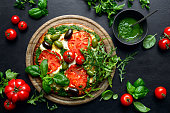 istock Pizza with green pesto and fresh tomatoes 1148189966