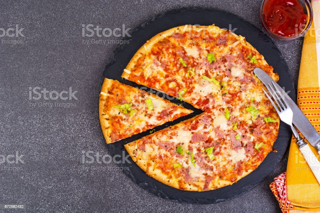 Pizza with ham and cheese on black stone stock photo