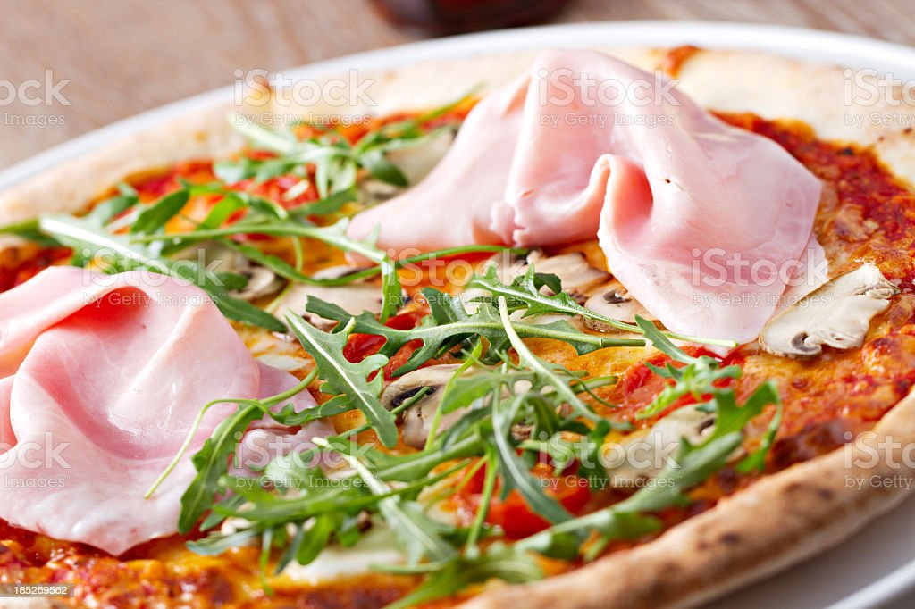 Pizza with ham mushrooms and rucola stock photo