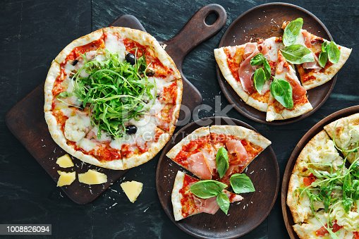 Pizza with ham, olive and arugula