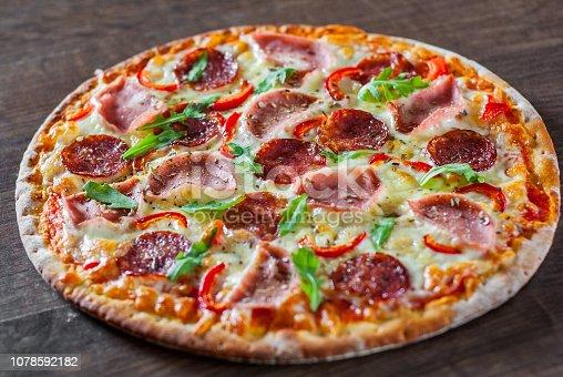 Pizza with Mozzarella cheese, ham, tomato sauce, salami, pepper, Spices and Fresh arugula. Italian pizza on wooden table background