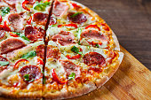 Pizza with Mozzarella cheese, ham, tomato sauce, salami, pepper, Spices and Fresh arugula. Italian pizza on wooden table background