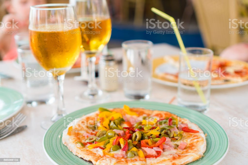Pizza with mozzarella cheese, olive, fresh tomato and pesto sauce. Served at restaurant table with two beers 免版稅 stock photo